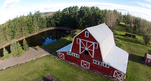 aerial drone image of red barn by a pond in dawson creek area